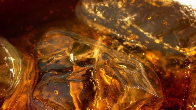 Two videos of cold cola with ice cubes in 4K