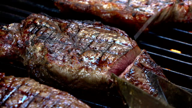 Two videos of cutting steak on the grill-real slow motion video