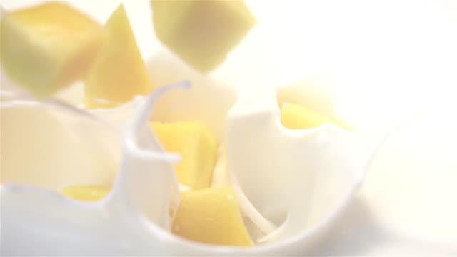 Two videos of mango falling into yogurt -real slow motion Two high quality videos of mango falling into yogurt in real 1080p slow motion 250fps mango stock videos & royalty-free footage