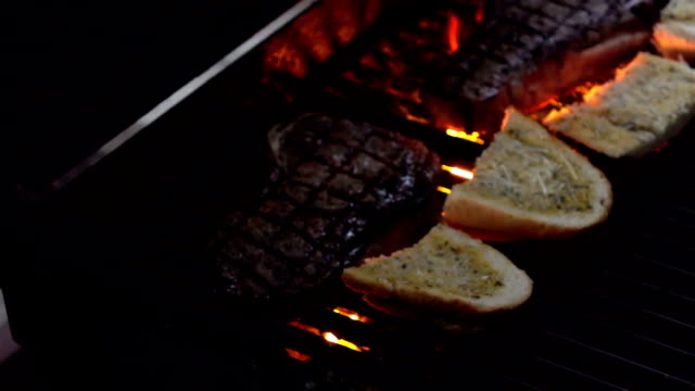 Two videos of opening grill with steaks and bread-slow motion video