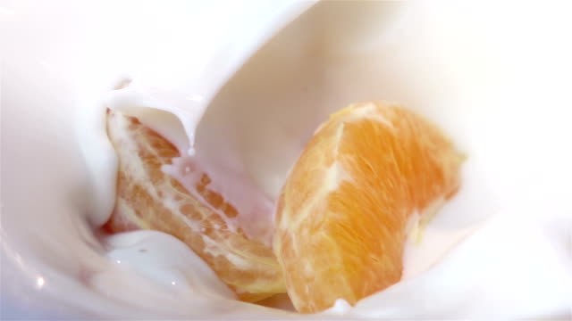 Two videos of pieces of orange falling into yogurt-real slow motion video