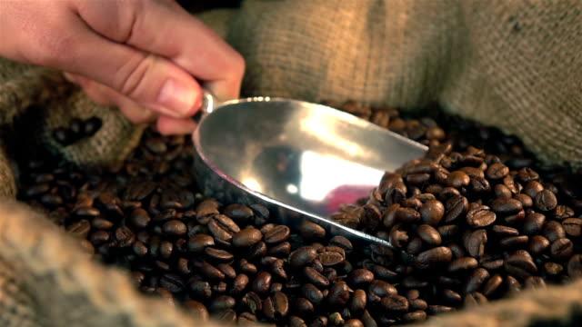 zwei videos von ausschöpfen kaffeebohnen in real zeitlupe - rohe kaffeebohne stock-videos und b-roll-filmmaterial