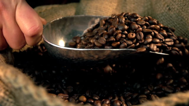Two videos of scooping coffee beans in real slow motion video
