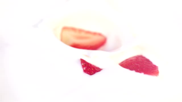 Two videos of strawberries falling into yogurt in real slow motion video