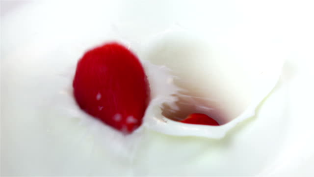 Two videos of strawberries falling into yogurt -real slow motion video