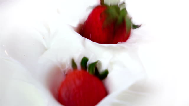 Two videos of strawberries falling into yogurt-real slow motion video