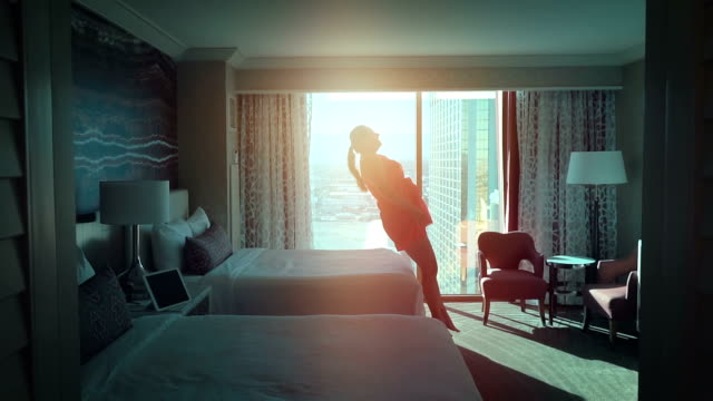 Two videos of woman jumping on the bed in real slow motion
