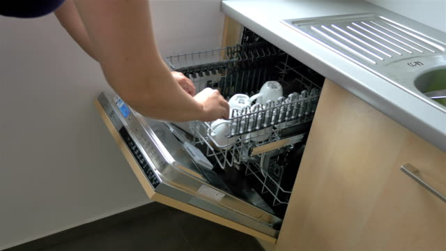 Two videos of woman putting dirty dishes to the dishwasher in 4K Two high quality videos of woman putting dirty dishes to the dishwasher in 4K dishwasher stock videos & royalty-free footage