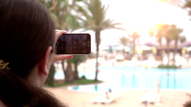 Two videos of woman taking a picture on vacation-slow motion video