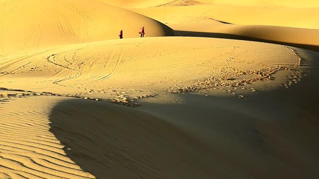 Two Vietnamese women carrying pole with wicker basket walking in desolate desert video