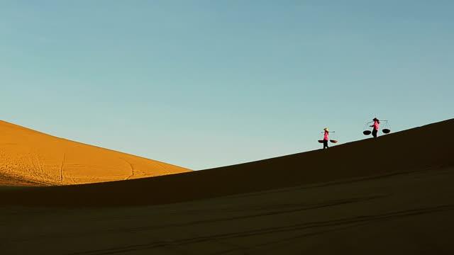 Two Vietnamese women carrying pole with wicker basket walking on sand dunes video