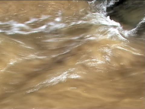 two views of sandy, dirty water flowing past - imperfection stock videos & royalty-free footage