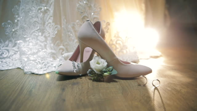 two wedding rings rolling together near bride's wedding shoes - wedding fashion stock videos and b-roll footage