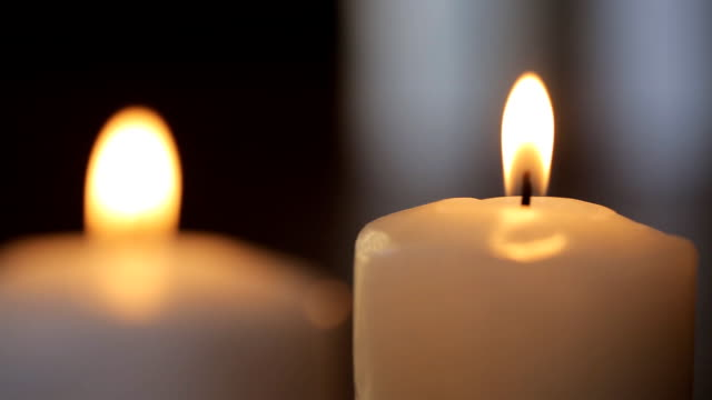 Two white candles burn in dark room to fill it with its light video