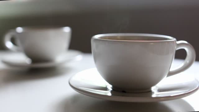 vidéos et rushes de deux tasses blanches de café plaçant ensemble sur la table blanche - boisson chaude