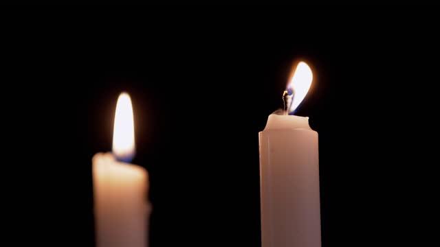 vídeos de stock, filmes e b-roll de duas velas brancas de parafina queimam com fogo amarelo, em um fundo preto. 4k - tradição