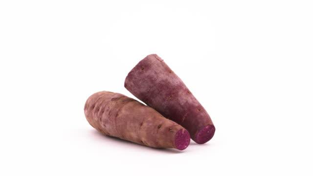 due patate dolci intere e una mezza viola che ruotano sul giradischi. isolato sullo sfondo bianco. primo piano. macro. - dolci video stock e b–roll
