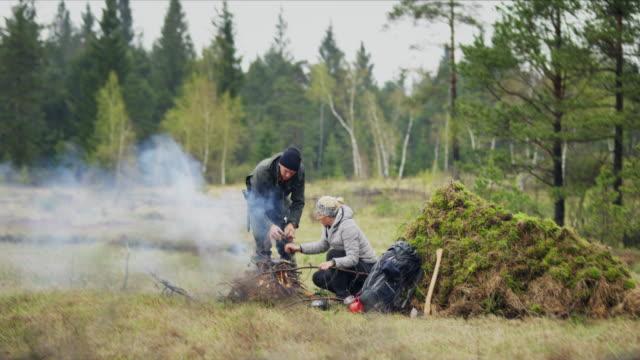ds i̇ki vahşi hayatta kalma uzmanları doğada bir yangın yapma - şömine odunu stok videoları ve detay görüntü çekimi