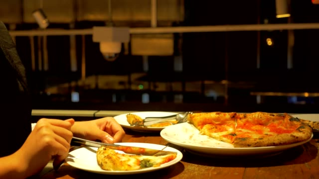 vídeos de stock, filmes e b-roll de duas mulher comer e tirar foto da pizza italiana impaciente - junk food