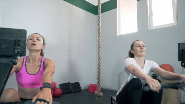 Two woman exercising on rowing machine. video