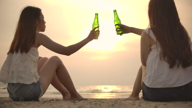 Two Woman friend Clinking beer bottle at sunset