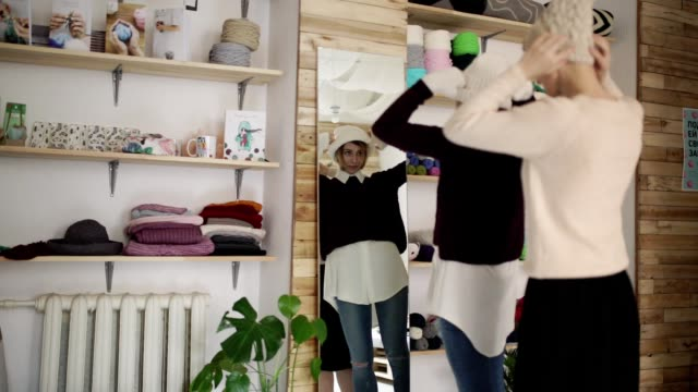 vídeos de stock e filmes b-roll de two woman friends fitting knitted cap front mirror in show room - roupa quente