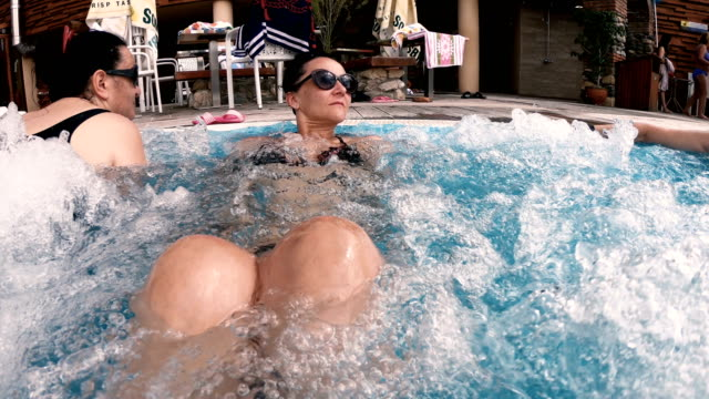Two woman having hydrotherapy  in thermal spa pool Hot tub