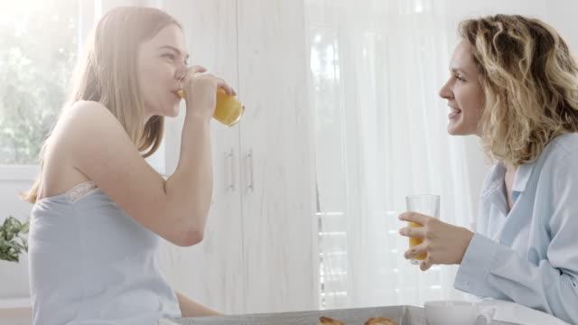 話、オレンジ ジュースを飲んでベッドで 2 つの女性 - 対面点の映像素材/bロール