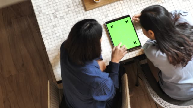 two woman looking at tablet green screen - compagni scuola video stock e b–roll