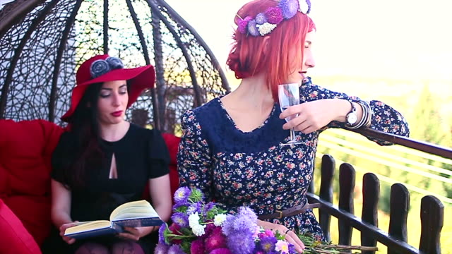 Two woman resting on a balcony and enjoying a book reading, conversation and view video