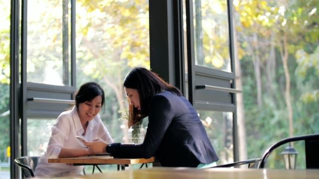 コーヒーカフェで仕事について話す2人の女性、スローモーション - カフェ文化点の映像素材/bロール