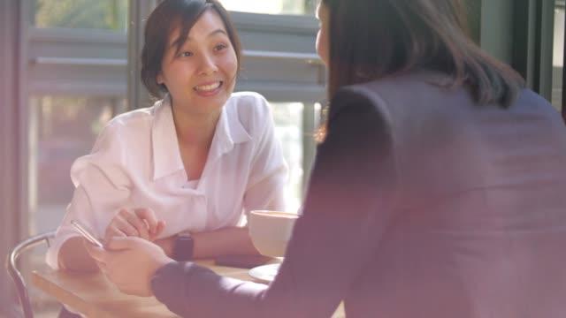 コーヒーカフェで仕事について話している2人の女性、スローモーション - カフェ文化点の映像素材/bロール