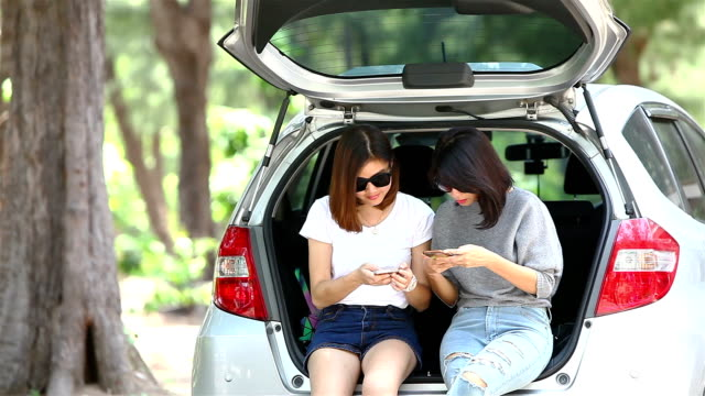 Two woman use mobile phone in the open back car video