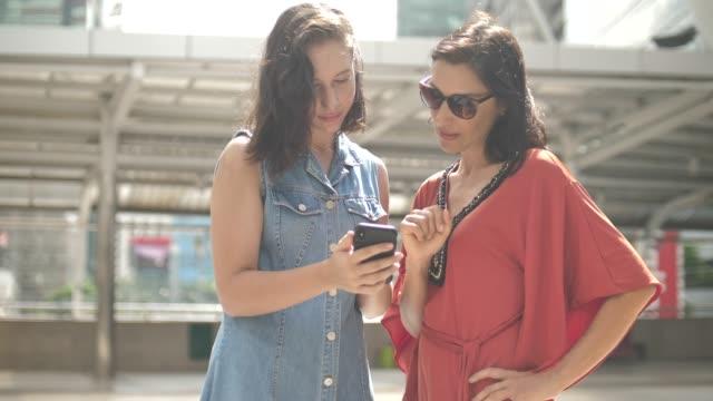 zwei frauen mit smartphone - teenage friends sharing food stock-videos und b-roll-filmmaterial