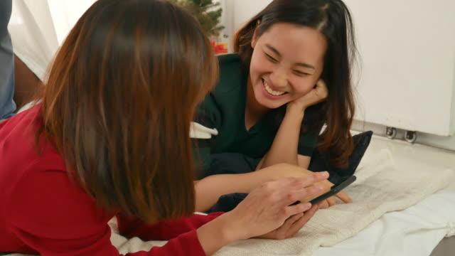 stockvideo's en b-roll-footage met twee vrouw met behulp van smartphone om te winkelen in kerst - oost azië