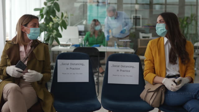 two woman with protective face mask and surgical gloves in bank waiting room - new normal video stock e b–roll