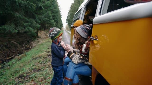 two women and little boy sitting in retro camper van - viaggio in macchina video stock e b–roll