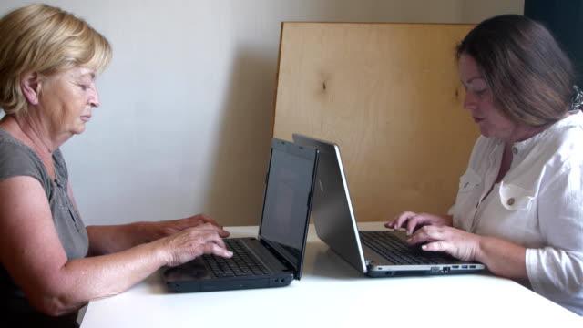 två kvinnor skriver bakom två bärbara datorer mittemot varandra - tjänstekvinna bildbanksvideor och videomaterial från bakom kulisserna