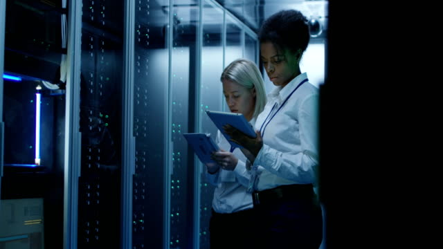 två kvinnor arbetar i ett datacenter med rader av serverrack - server room bildbanksvideor och videomaterial från bakom kulisserna