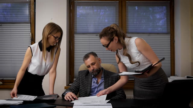 Two women assistants to apply for signature to his boss. A respectable businessman with gray hair is in its solid cabinet video