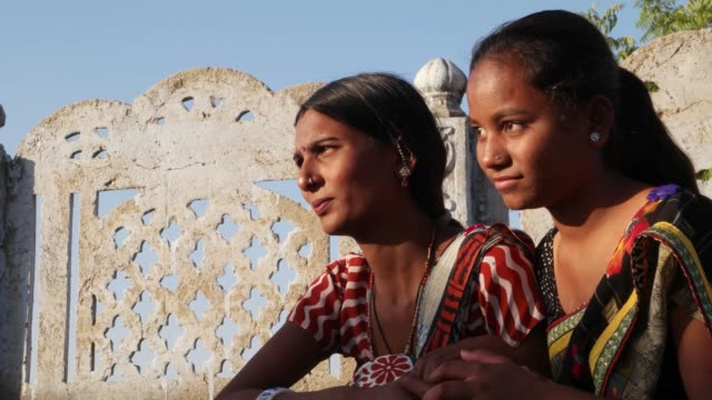 two women bonding talking sharing sitting staring in same place side-profile on a terrace in traditional dress in india handheld  two medium shot love tradition rural outdoor summer heat sun - sari filmów i materiałów b-roll