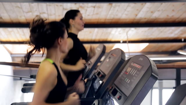 Two women brunette smiling and running on a treadmill simulator video
