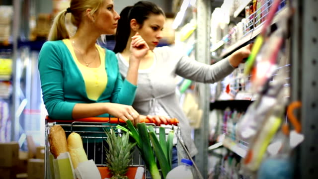 Two women buying cosmetics in supermarket. video