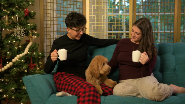 Two Women Celebrating Christmas with Their Puppy and Hot Cocoa