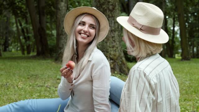 zwei frauen plaudern während des picknicks - peach stock-videos und b-roll-filmmaterial