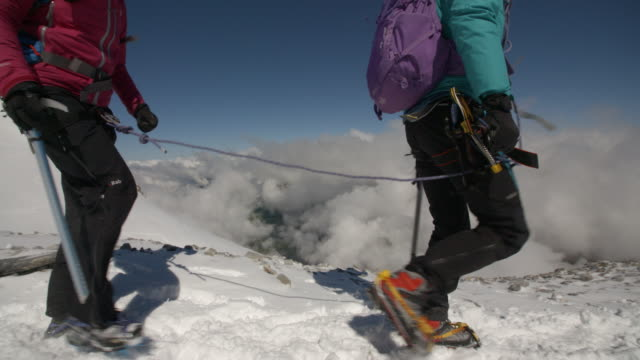 Two women climbing a mountain above the clouds with ice axes and crampons in slow motion. video