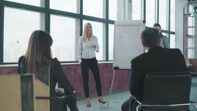 2人の女性の同僚がフリップチャートの近くでグラフィックについて話し合い、聴衆とコミュニケーションをとり、手をたたきます。クリエイティブなコワーキングスペース。ビジネスインテ ビデオ
