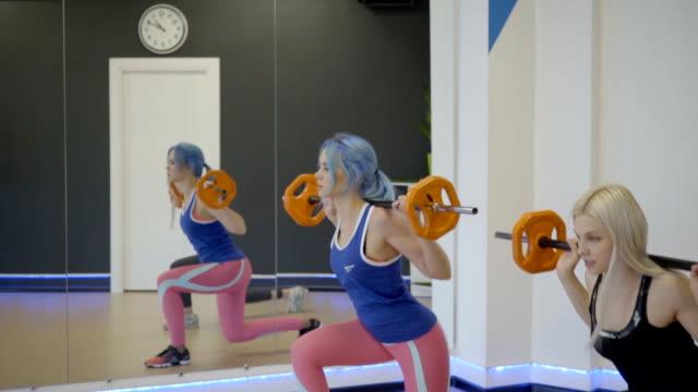 Deux femmes faisant des flexions avec haltères en gym - Vidéo