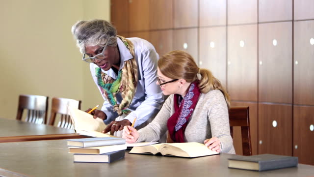 Two women doing research together in library