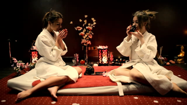 Two women drink herbal tea and talk. video